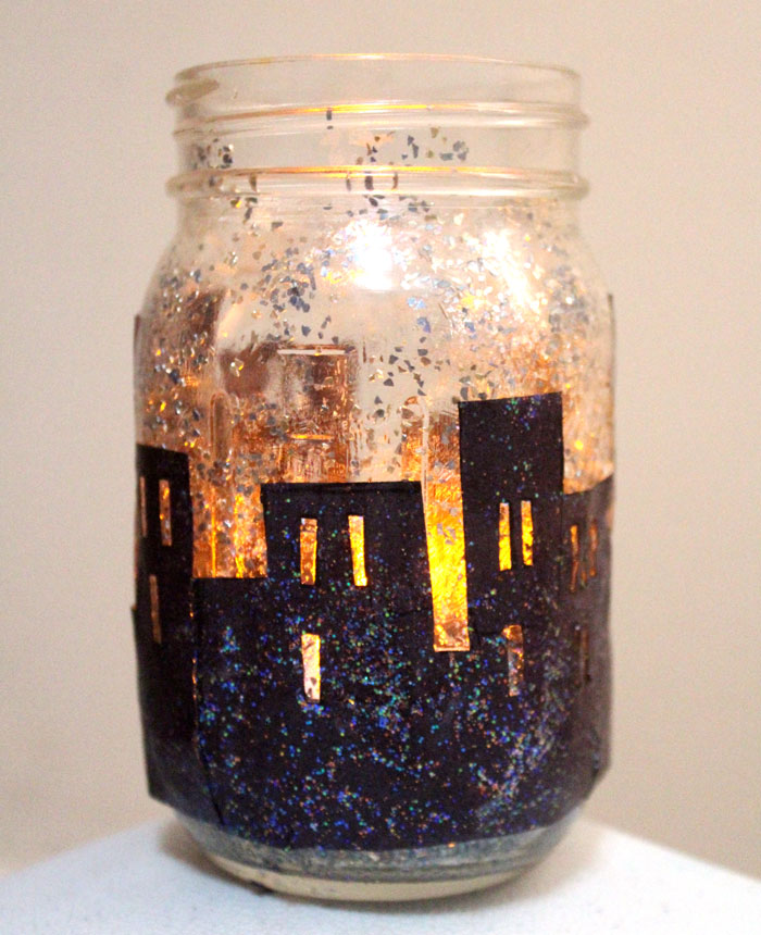 Make this magnificent DIY snowy skyline winter lantern - don't you love how the light shines though the windows on this recycled mason jar craft?