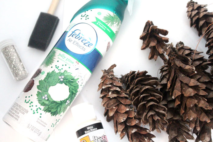 Make this beautiful snowy pine cone wall hanging! Such a pretty and easy winter craft to decorate your home. Plus, how to add a matching aroma to your decor!