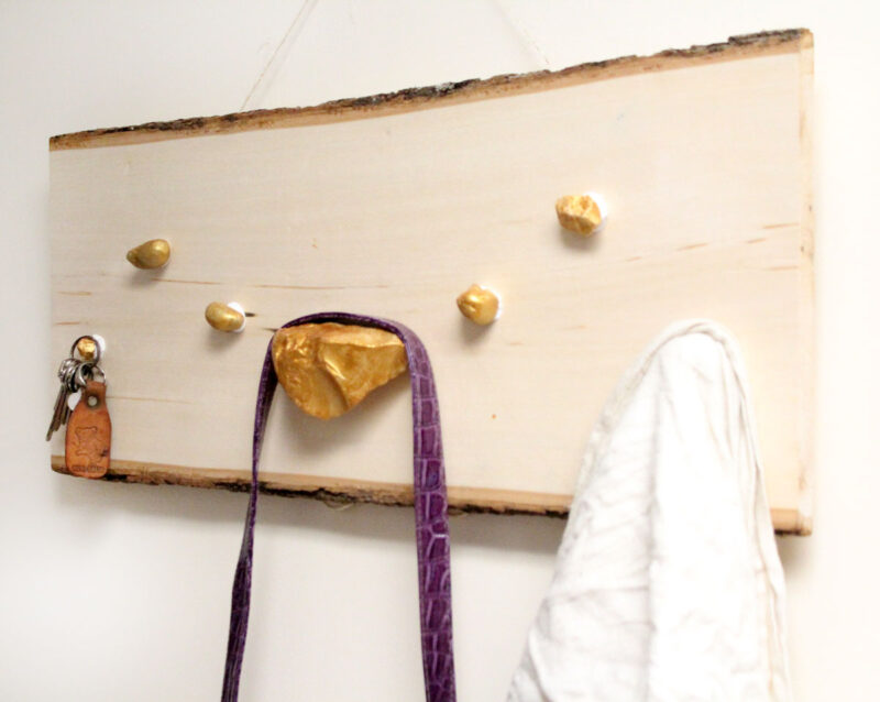 I LOVE how easy it is to make this DIY key and accessory organizer. What a great idea to declutter an entryway. IT will fit a rustic or natural home decor theme, with a touch of metallic gold too. Such a great entry organization idea - and it uses rocks, which are stuck WITHOUT TOOLS - how cool?!