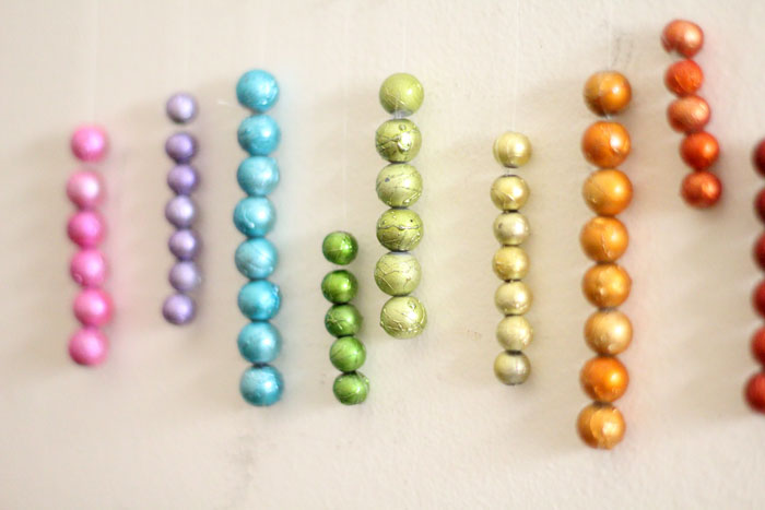 This beautiful DIY garland seems to disappear on the wall, leaving you with the hanging beaded strands! Such a cool effect. Make this easy beaded rainbow garland as a regular home decor staple or as a cool sukkah decoration craft.