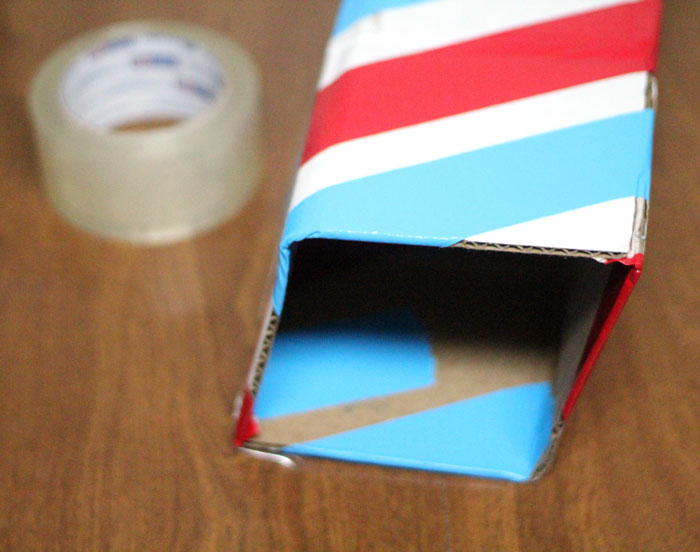 Make this barber shop pole centerpiece for you haircut party! This cool barber shop party decor idea is easy to make, mess-free, and uses recycled materials and is a great, easy upcycled cardboard box craft idea!