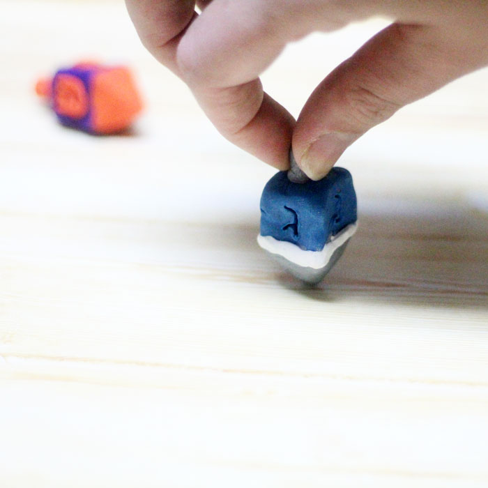 How to make a dreidel out of clay a perfect craft for Hanukkah! You can totally do these as a chanukah party activity since they don't take too long to bake and make a cool gift for kids as well.