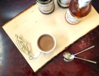 Make this beautiful rustic and easy DIY coffee bar tray - it' super easy! It's great for setting up a coffee bar in the kitchen or a flavoring station at a party or a wedding, and corrals syrups and flavorings in a small space. It has a farmhouse style to it, with a bit of glam added in - just choose the handles to suit your decor!