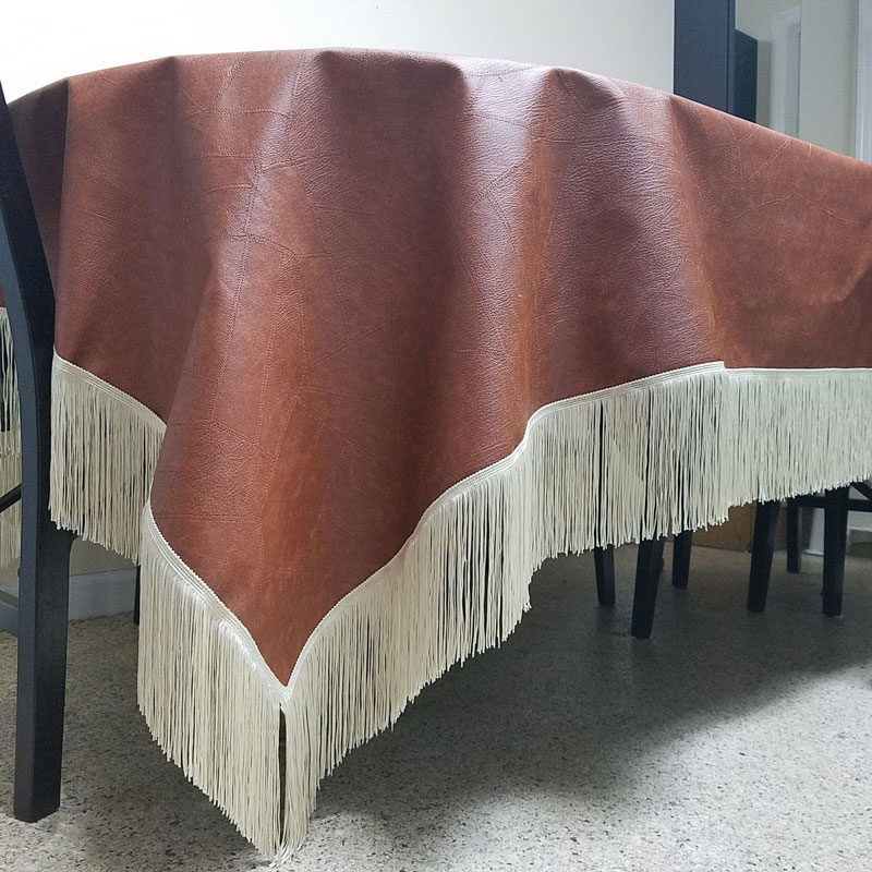 A faux leather table cloth - how brilliant is that?! Make this super easy no sew DIY leatherette tablecloth so your kids don't mess up your good one. It doesn't look tacky like other vinyl table covers, and is a brilliant holiday tablescape idea or kid-friendly decor!