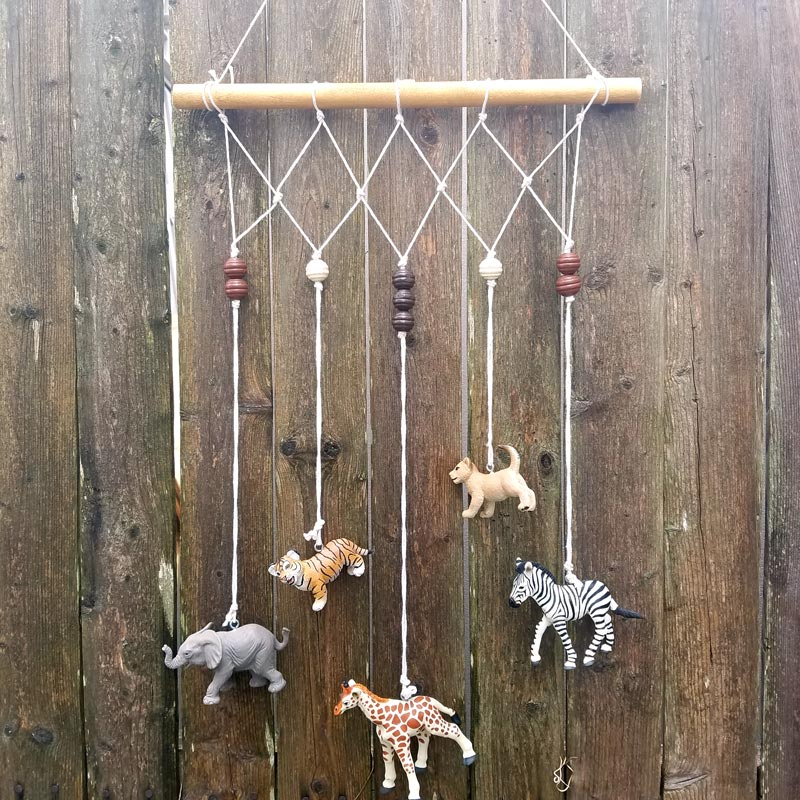 Make an adorable animal wall hanging for the kids room or nursery! Turn toy animals into beautiful playroom decor - and when your'e ready to redecorate, it can be repurposed as a toy! Love this safari animal kids bedroom decor idea - it's such an easy DIY decor craft!