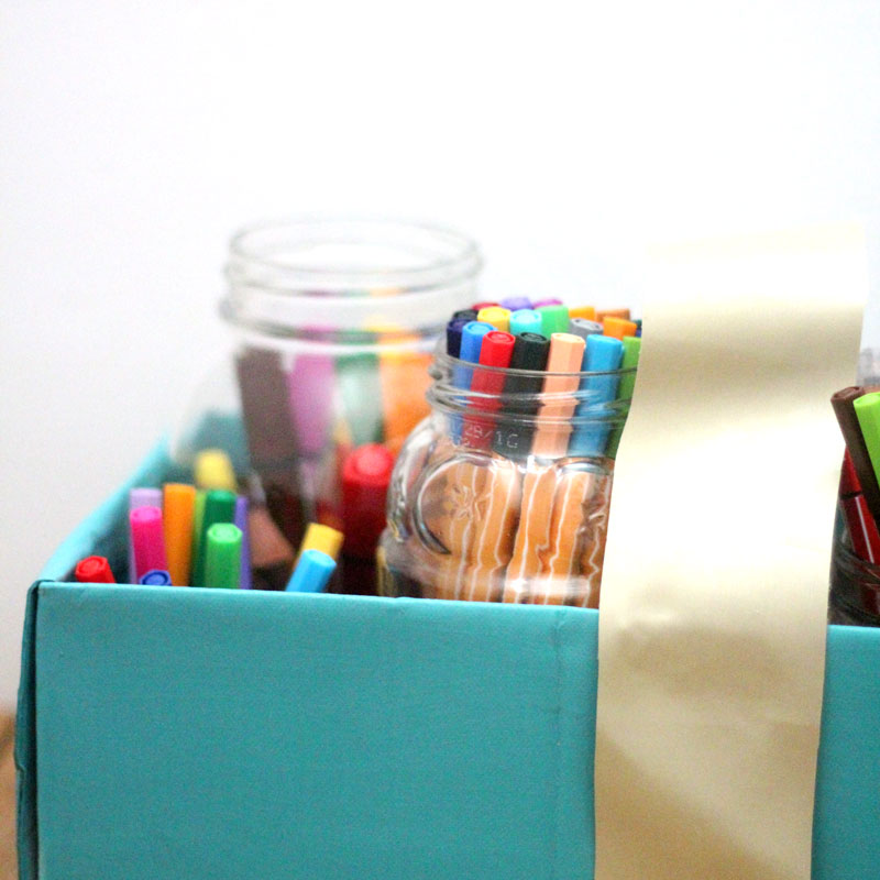 Make a super easy upcycled DIY marker storage caddy to transport the entire family's art supplies from the closet to the table in a usable bin! The jars can be removed individually to easily set up and clean up a family art station with coloring supplies for kids and adults. This recylced cardboard box and jar craft is so easy to make, and is an awesome craft room organization hack.