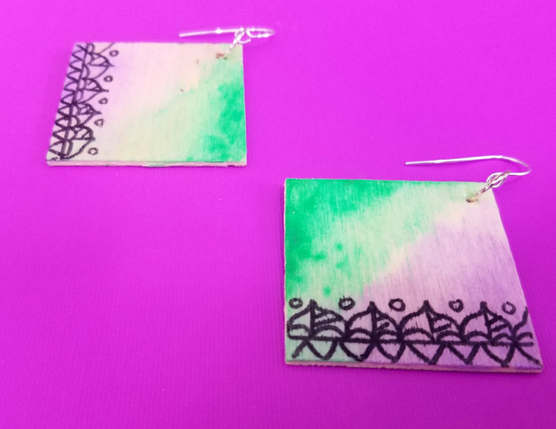 Make these stunning DIY earrings with a watercolor finish and some cool doodles! You'll love this beginner jewelry making project for teens and tweens to enjoy.