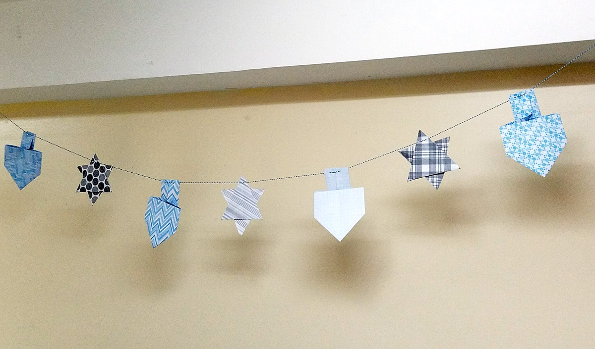 Make a fun origami Hanukkah garland featuring folded paper dreidels and star of david. This simple Chanukah craft for kids teens and adults is a perfect way to update your Hanukkah decor.