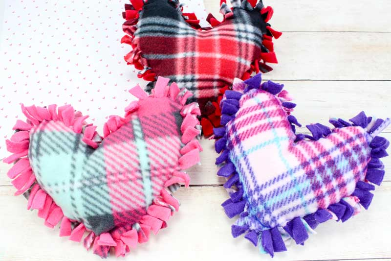 These valentine pillows are so easy to make! They use the classic summer camp fleece tie pillows method and are the perfect Valentine's Day crafts for tweens and big kids. #tweens #teencrafts #valentinesday