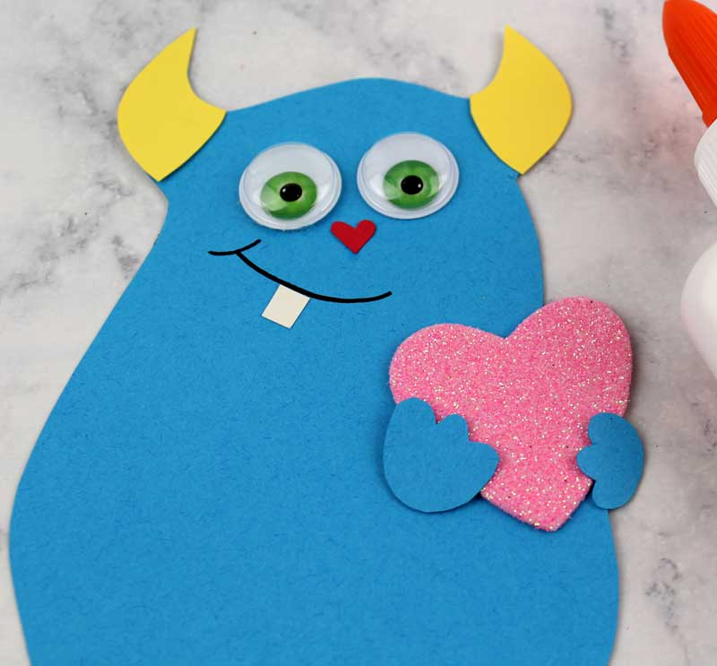 These adorable Monster love valentine treat bags are perfect for favors or snacks! This cute Valentine's Day paper craft is also good for a monster birhtday party. It doesn't have to have the heart, and you can put any shape in the monster's hands. #papercraft #valentinesday #valentine