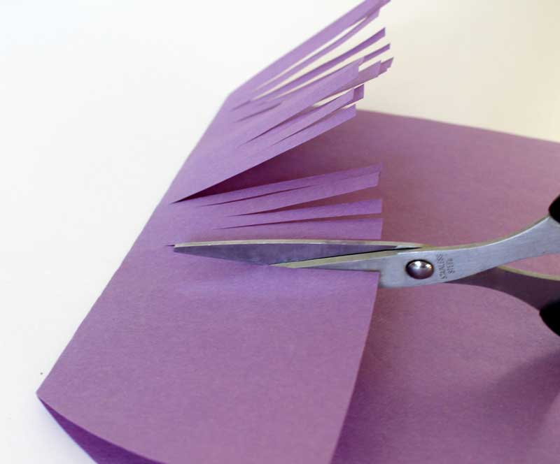 Step 5. Make cuts in the construction paper flap to create hair in the bangs. You can allow your child to do this part too!
