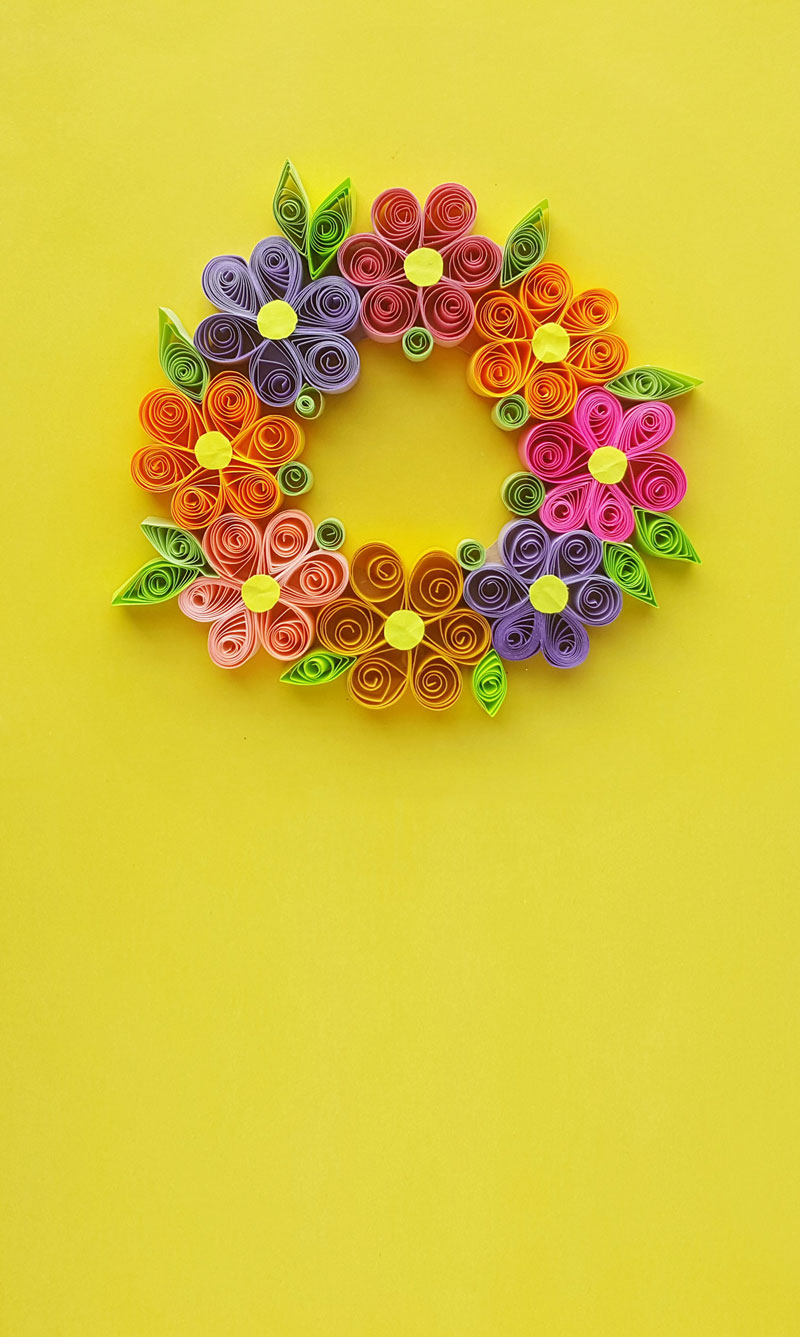 Make a beautiful floral Spring wreath - a cool DIY paper craft for Spring. This paper quilling wreath is fun for teens and tweens and to learn basic paper quilling designs techniques and patterns.